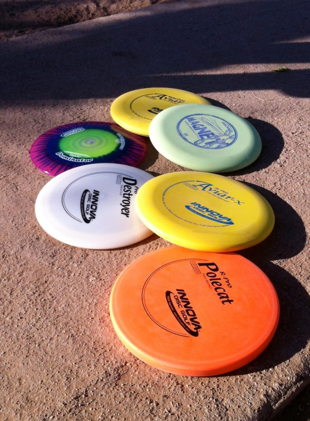 Array of disc golf equipment (half are friend Josh's).